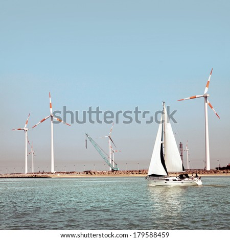 Cargo sea port. Wind turbines. Sea. Yacht.