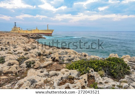 Cargo ship aground near rocky coast - stock photo