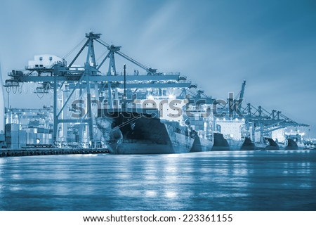 Cargo ship and crane at port reflect with water, twilight time (blue color tone). - stock photo