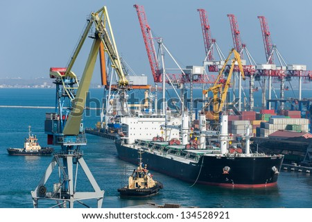 cargo ship and tug boat in port - stock photo