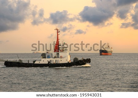 Cargo Ship and Tugboat in the morning - stock photo