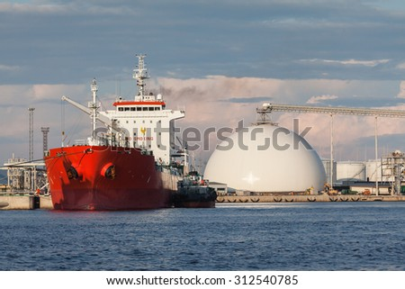 Cargo ship and white tanks with chemicals in Riga port Fertilizer terminal, situated at the water bank of Daugava river in Latvia.