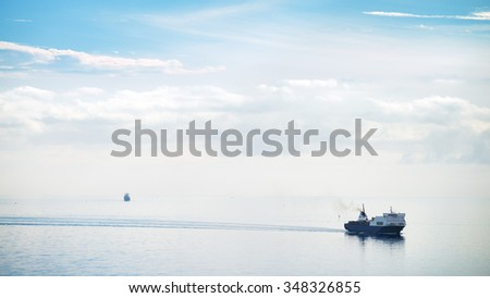 Cargo ship approaching the harbor on a day of quiet total - stock photo