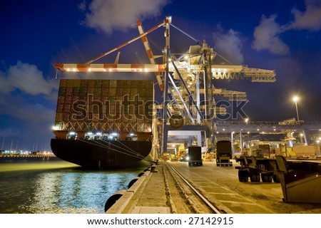 cargo ship at dock by night from behind - stock photo