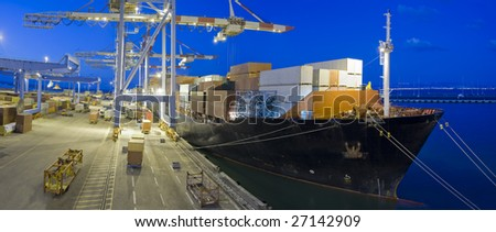 cargo ship at dock by night panorama - stock photo