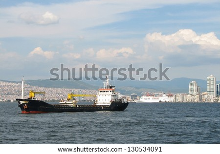 Cargo ship at Izmir's bay and liner on background