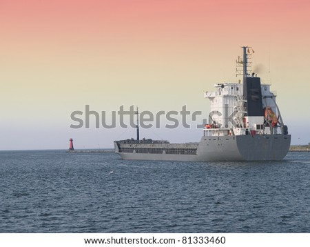 Cargo ship at sunrise - stock photo