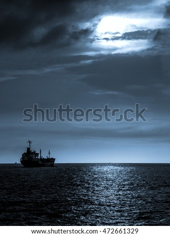 Cargo ship at sunset in blue tone