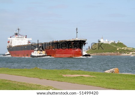 Cargo ship being escorted to the Newcastle harbour, Australia - stock photo