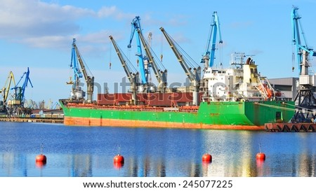 Cargo ship (Bulk carrier) loading in cargo terminal of Riga - stock photo