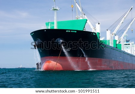 Cargo ship drain water to the Ocean - stock photo