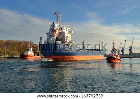 Cargo ship entering Gdansk harbour - stock photo