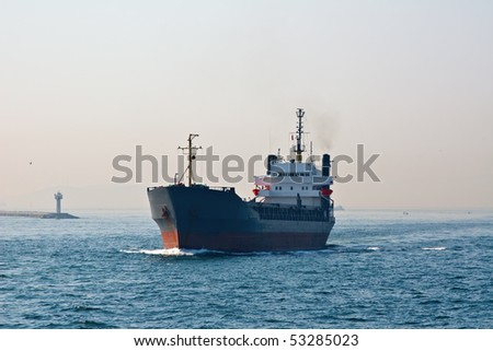 Cargo ship entering Istanbul harbour in the morning haze - stock photo