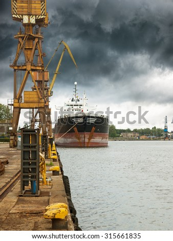 Cargo ship in port at cloudy day. - stock photo