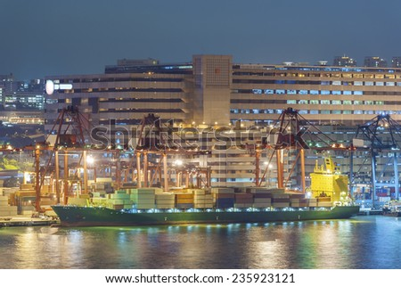 Cargo ship in port in Hong Kong at night - stock photo