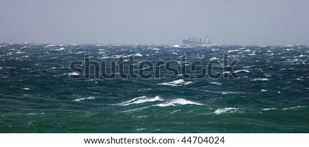 Cargo ship in storming sea - stock photo