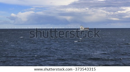 Cargo ship in the sea with electricity windmills in the background in sunny day
