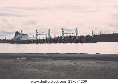 cargo ship is leaving port sailing away. riga. latvia - retro, vintage style look - stock photo