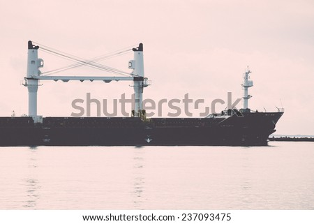 cargo ship is leaving port sailing away. riga. latvia - retro, vintage style look - stock photo