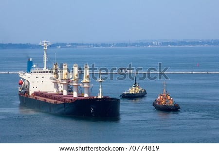 Cargo ship leaves port with tugs assistance - stock photo