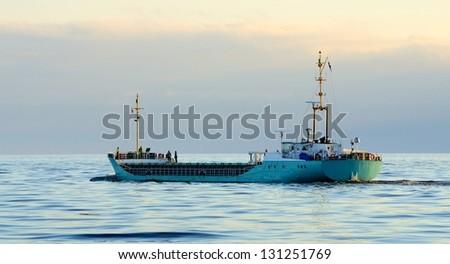 Cargo ship leaving port - stock photo