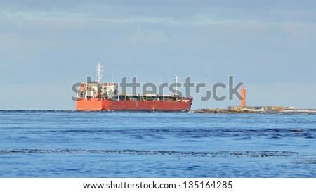 Cargo ship leaving port with lighthouse at the background