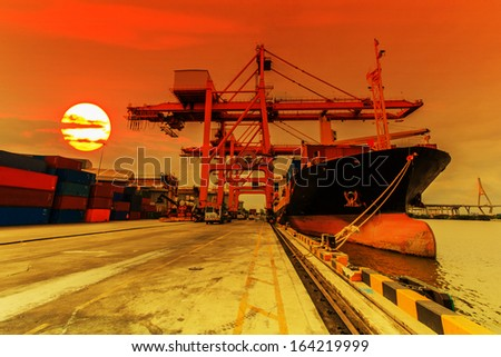 Cargo ship loading containers at sunset  - stock photo