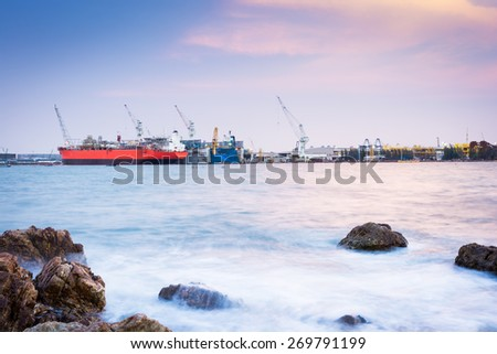 Cargo ship loading in cargo terminal and sunset of Thailand - stock photo