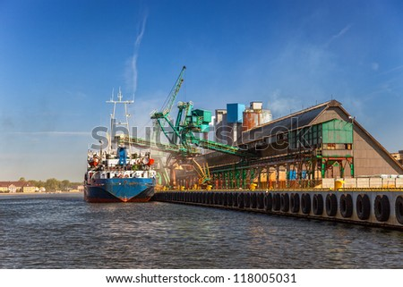 Cargo ship loading on the dock in port of Gdansk, Poland. - stock photo