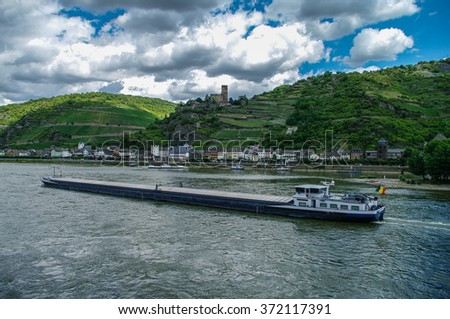 Cargo ship on Rhine river. Germany. Romantic Gutenfels medieval castle, hills with the famous vineyards of the Rhine and medieval village on background. - stock photo