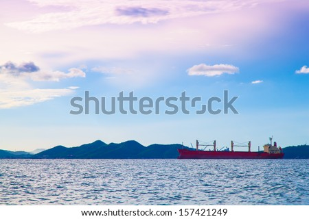 cargo ship Parked in the middle of the sea. Morning clouds and sky. - stock photo
