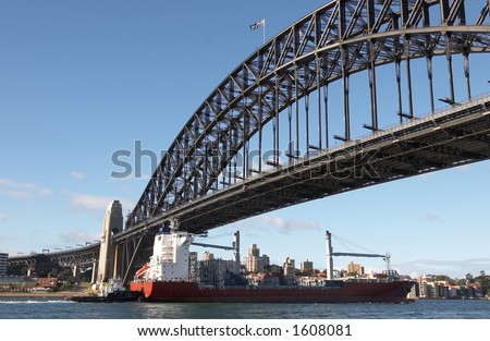 Cargo ship passing under the Sydney Harbour Bridge
