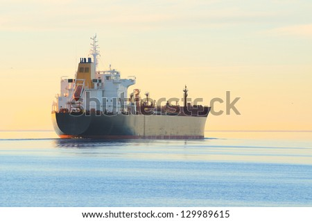 Cargo ship sailing away at the colorful sunset