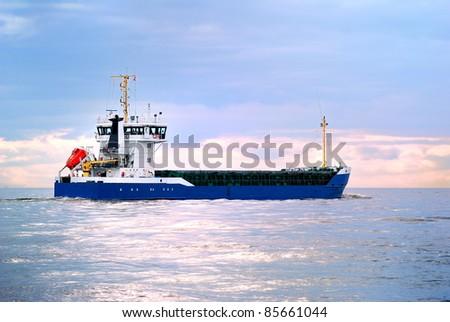 cargo ship sailing heading for the sunset. Port of Riga, Latvia - stock photo