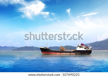 cargo ship sailing in still water - stock photo