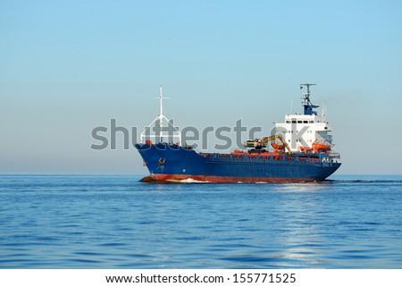 cargo ship sailing in still water - stock photo