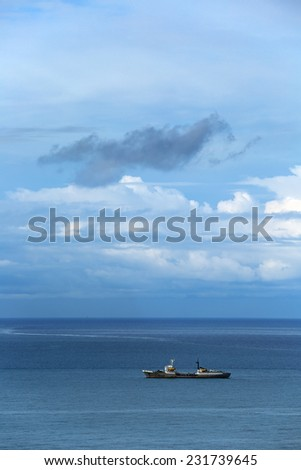 Cargo ship sailing in the sea on the backdrop of a cloudy sky