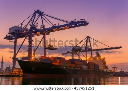 Cargo ship terminal at twilight scene, Unloading crane of cargo ship terminal, Sunrise shot. - stock photo