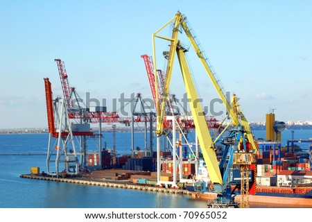 Cargo ship under crane bridge in harbor - stock photo