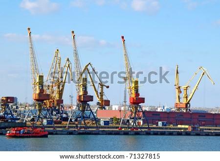 Cargo ship under crane bridge in harbor - stock photo
