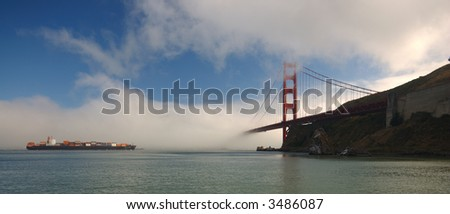 Cargo ship with containers stacked high on deck approaches Golden Gate Bridge while fog is blowing into San Francisco Bay.
