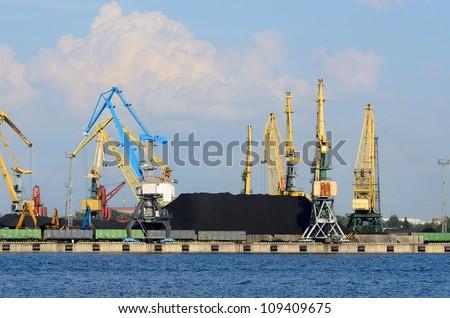 Cargo terminal of Riga, Latvia. Wide view with cranes loading coal - stock photo
