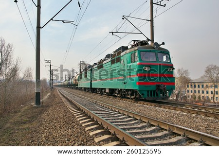 Cargo train driving along the track on the embankment - stock photo