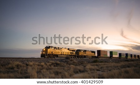 Cargo train traveling through desert. - stock photo