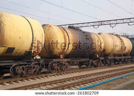 Cargo train with oil tanker cars carrying the fuel on the railway track - stock photo
