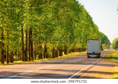 cargo truck driving on suburban highways in summer - stock photo