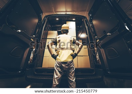 Cargo Van Delivery. Rear Cargo Doors Reloading. Construction Guy Talking Care of Fresh Supplies Delivery. Large Cargo Van with Many Cardboard  Boxes Waiting For Reload. - stock photo