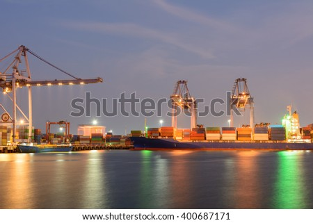 Cargo vessel and large crane operating at the seaport during twilight time - stock photo