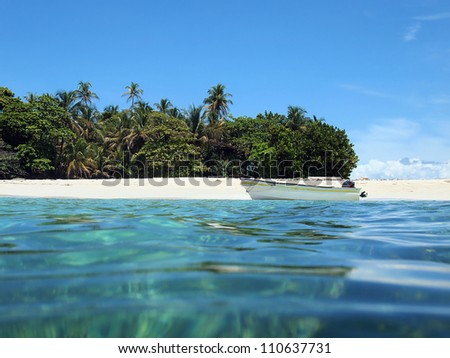 Caribbean beach on a island with tropical vegetation and a boat on the shore seen from sea surface