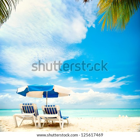 Caribbean Beach.Paradise. Vacation and Tourism concept. Sunbeds and Palm tree - stock photo